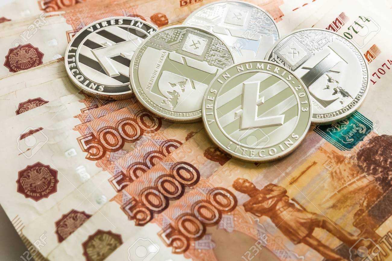 Silver crypto coins Litecoin LTC, paper denominations of Russian rubles. Metal coins are laid out in a smooth background to each other, close-up view from the top, crypto currency exchange of money.